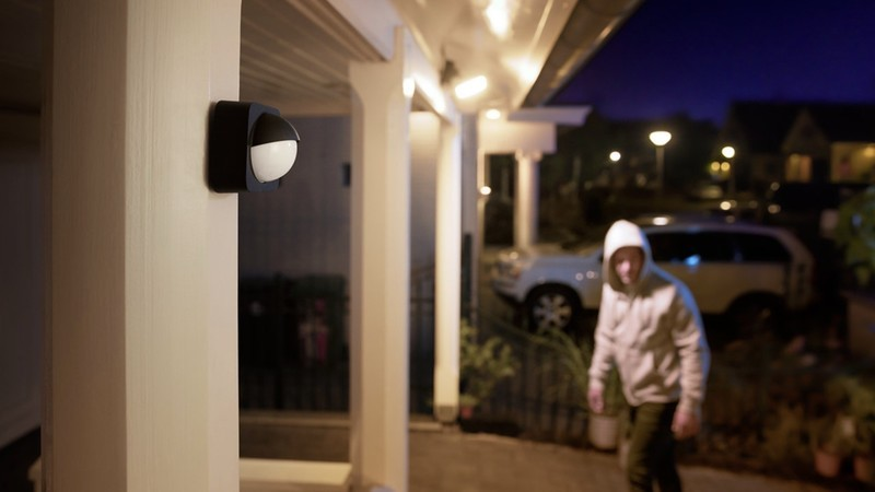 Philips Hue Outdoor Motion Sensor installed outdoors overlooking a home's entrance