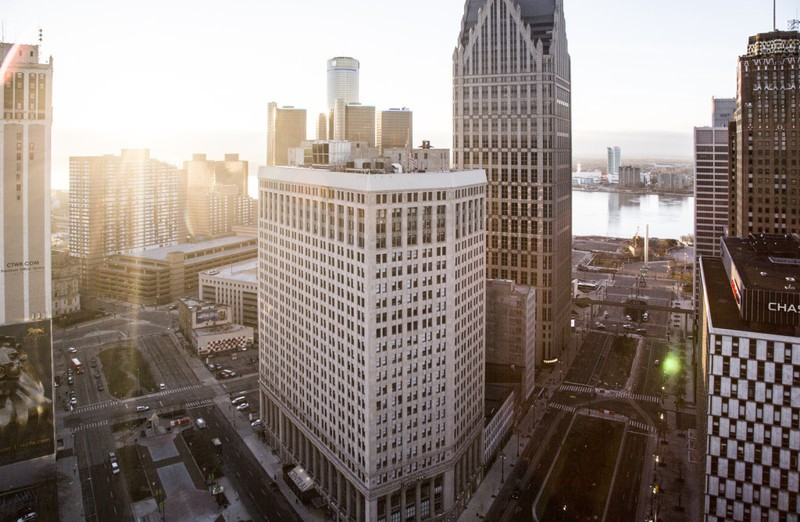 Downtown Detroit from the rooftop of 1001 Woodward during sunrise. From left to right: The First National building, Renaissance Center, One/Ally Detroit Center, Woodward Avenue, the Detroit River, Har