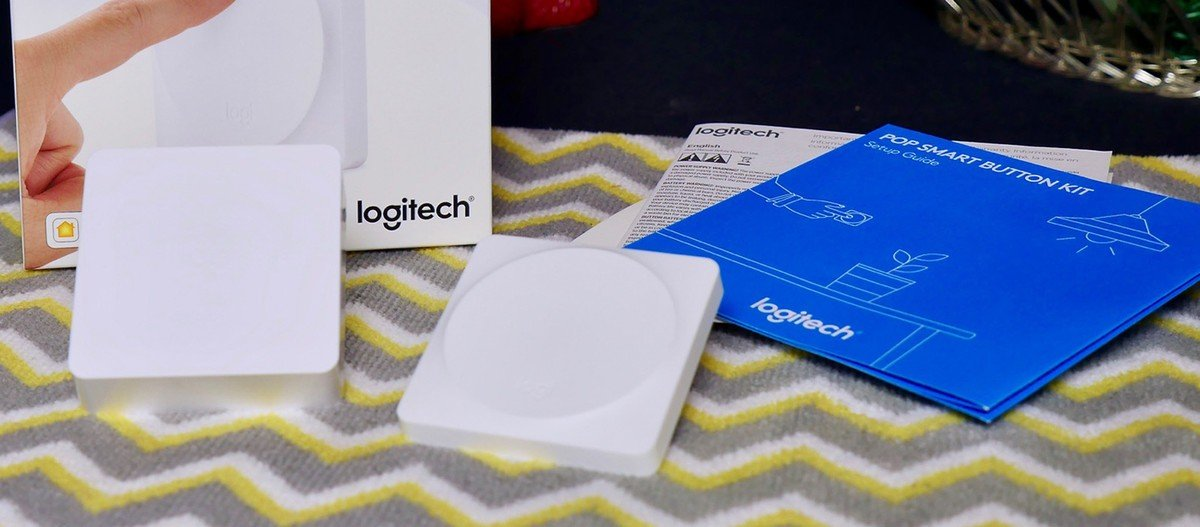 The Logitech POP Smart Button sits beside the HomeKit-enabled POP bridge, a startup guide, and the box in which everything came.