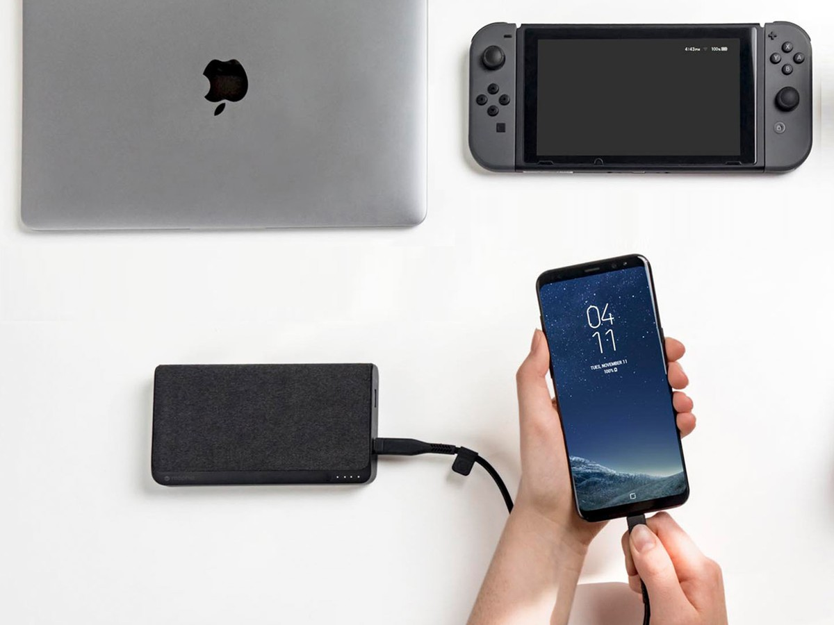 A Mophie Powerstation USB-C XXL is shown charging an Android phone. A MacBook Pro and a Nintendo Switch sit in the background.