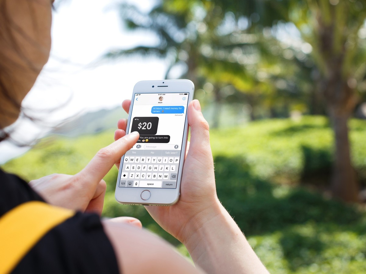 An individual holds an iPhone in their hands, and an Apple Pay Cash transaction in iMessage is shown on the screen