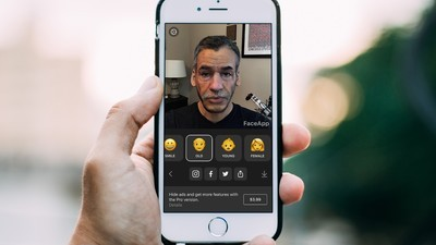 An iPhone is shown in a person's hand. The FaceApp is launched and one of two smile filters has been applied to the person's face.