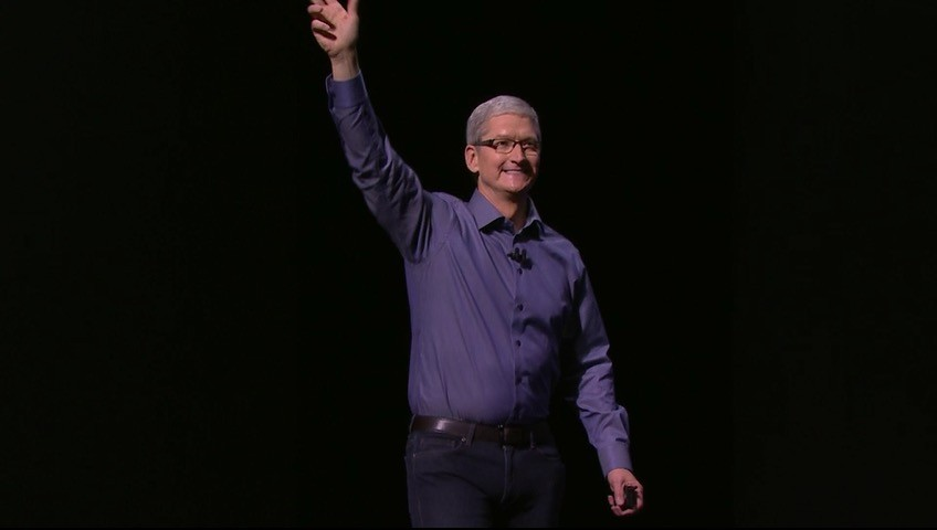 Tim Cook waves his hand at the audience during an Apple press event.