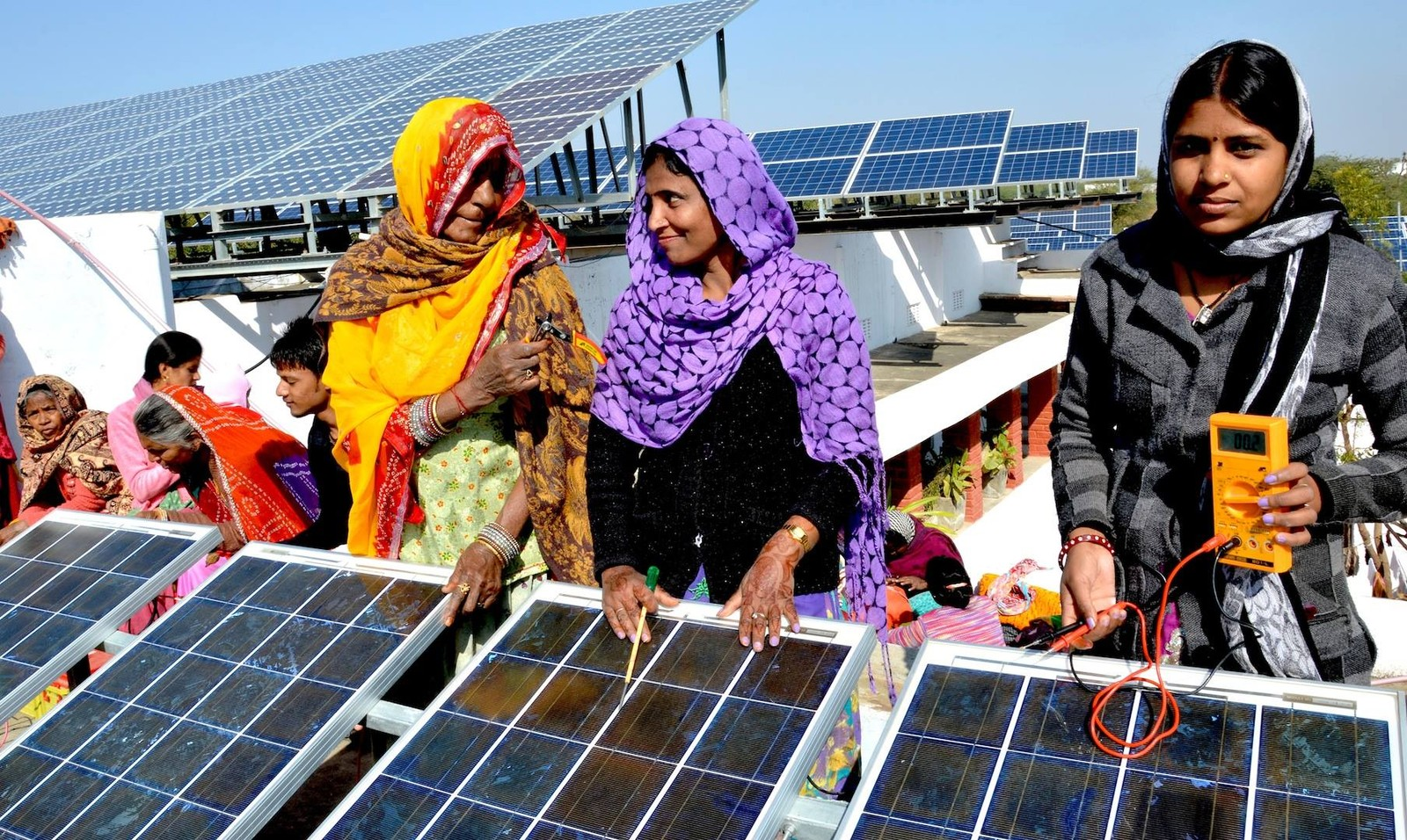 Women stand behind a solar panel in an image taken for Barefoot College in India.