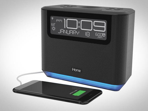 the iAVS16 alarm clock and an iPhone sit on a white surface