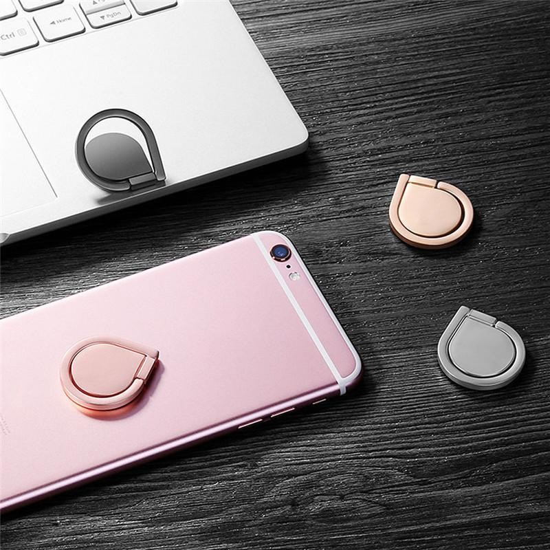 A pink iPhone and a silver MacBook sit on a dark wooden table surrounded by fidget spinner grip rings
