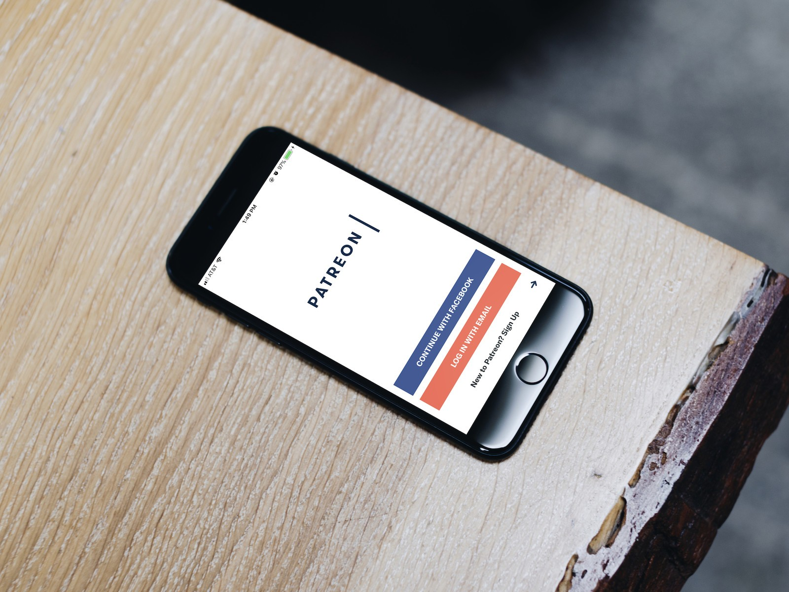 A black iPhone on a wooden surface with the Patreon app pulled up on the screen